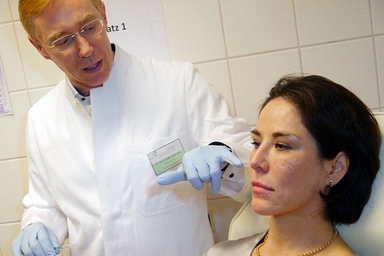 """Dr. Müller-Steinmann demonstriert, wie durch die Injektions-Lipolyse kleinere Fettpölsterchen abgeschmolzen werden können - ein weiterer Baustein des """"Face Design""""."""